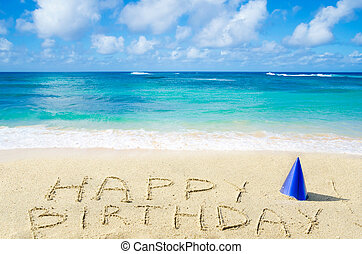 """Sign """"Happy Birthday"""" with hat on the sandy beach by the ocean"""