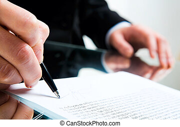 Closeup of business lady�s hand with pen signing a contract on the background of her other hand touching the table