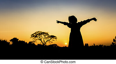 Silhouette freedom a Little girl at sunset