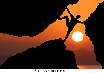 Silhouette man Climbing between rocks with red sky sunset background