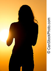 Silhouette of a beautiful girl at sunset