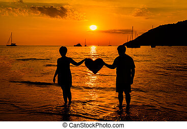 Silhouette of a couple on the beach at sunset
