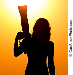 Silhouette of a girl photographer at sunset