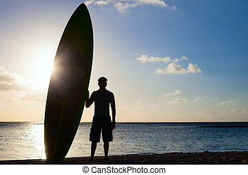 Silhouette of a man with paddle board