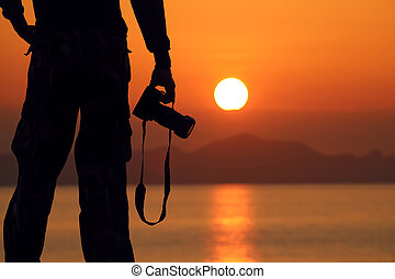 Silhouette of a photographer holding professional camera on the beach