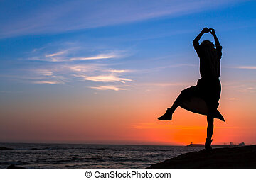 Silhouette of a young fun woman on the sea beach at amazing sunset.