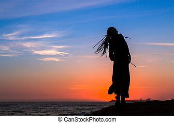 Silhouette of a young fun woman on the sea beach at sunset.