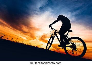 silhouette of biker boy riding mountain bike on hills at sunset