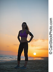 Silhouette of fitness young woman standing on beach at dusk