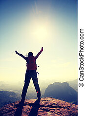 silhouette of free cheering woman hiker open arms at mountain peak
