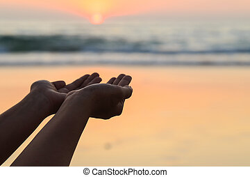 Silhouette of hands play with the sun at neach in sunset time