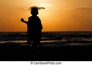little girl on a beach at sunset
