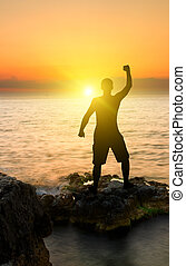 silhouette of man on the sunset ocean background