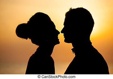 Silhouette of romantic couple on the beach at sunset