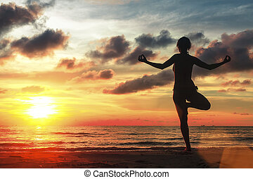 Silhouette of woman standing at yoga pose on beach during amazing sunset.