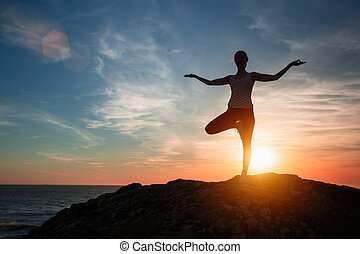 Silhouette of woman standing at yoga pose on the sea beach during sunset.