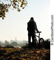 Silhouette of woman with bicycle by the break of day