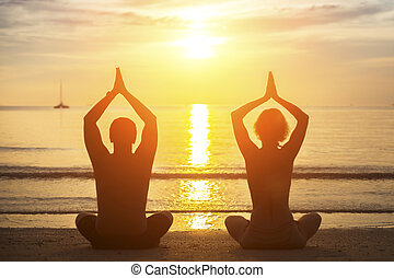 Silhouette of young couple practicing yoga on the beach during sunset.