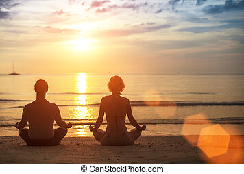 Silhouette of young couple practicing yoga on the sea beach at beautiful sunset.