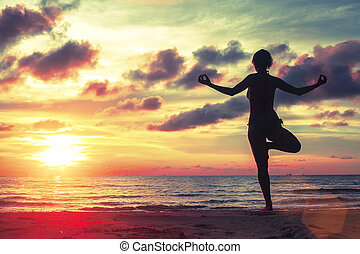 Silhouette of young girl standing at yoga pose on the beach during an amazing sunset.