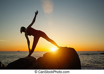 Silhouette of young woman doing fitness exercises on the beach at amazing sunset. Yoga and health.