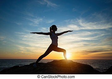Silhouette of young woman practicing yoga standing in warrior pose on the beach at sunset.