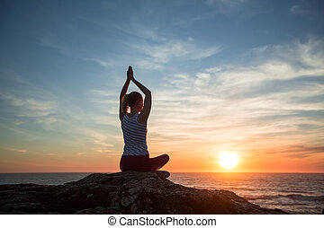 Silhouette of young yoga woman meditation on the ocean beach at amazing sunset.