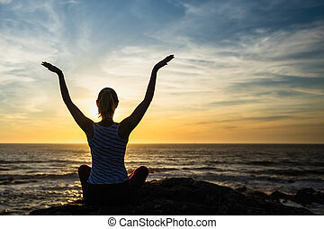 Silhouette of young yoga woman on the beach at amazing sunset.