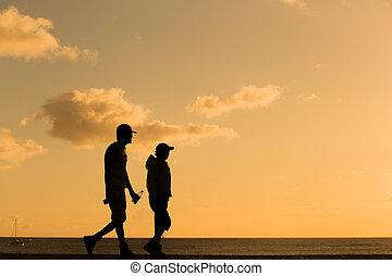 Silhouette people walking at sunset