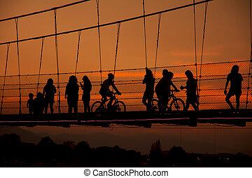 silhouette people walking on rope b