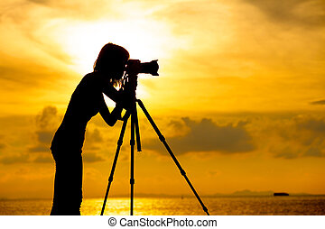 Silhouette photographer at sunset