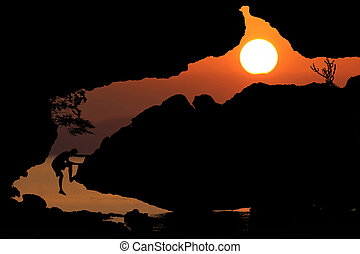 Silhouette rock climbing with red sky sunset background