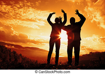 silhouettes young woman and man on a sunset