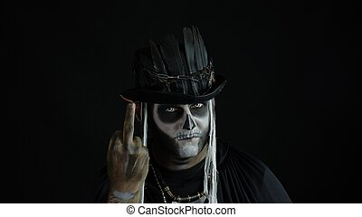 Sinister man with skull makeup making faces and showing middle finger. Bad manner gesture. Halloween