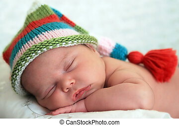 Sleeping baby girl wearing a striped hat