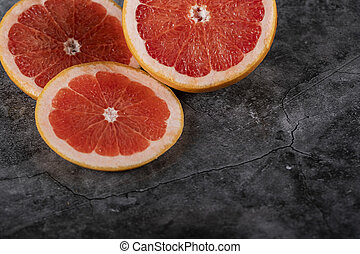 Sliced juicy fresh grapefruit on a dark background