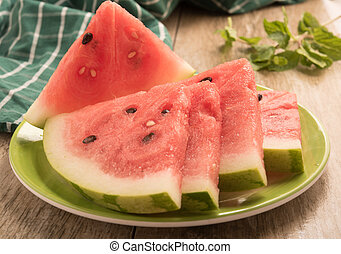 sliced watermelon arranged in a green plate on a black background