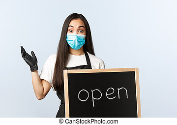 Small business, covid-19 pandemic, preventing virus and employees concept. Rejoicing cafe employee, store owner showing open sign and celebrating, wear medical mask and gloves