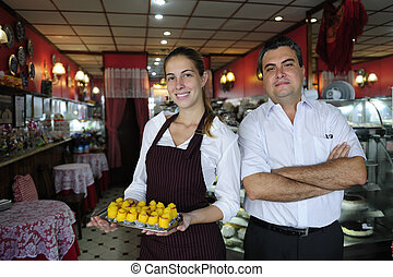 small business: owner of a cafe and waitress with pastry