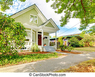 Small cute craftsman American house wth green and white and red door.
