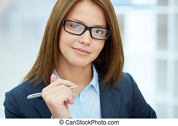 Portrait of young businesswoman in eyeglasses looking at camera