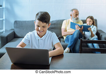 Smart youngster grinning widely while working on laptop