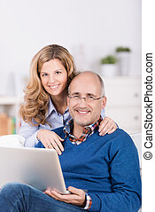 Smiling affectionate couple using a laptop