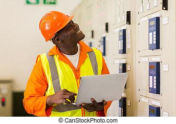 african male industrial engineer using laptop