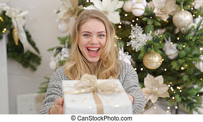 Smiling and happy young woman with christmas present box near christmas tree.