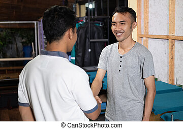 smiling Asian male owner shaking hands when meeting customers