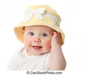 Smiling baby girl showing tongue wearing a yellow hat isolated on white background