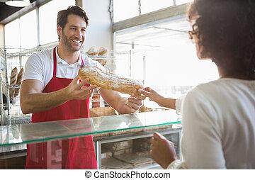 Smiling baker doing loaf transaction with customer