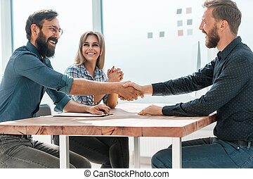 smiling businesswoman shaking hands with her business partner