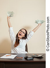 Smiling businesswoman throws up a pack of dollars